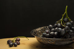 Antique fruit bowl with cluster of grapes Stock Photo