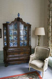 Antique furniture. Old fashioned interior with upholstered chair and antique cabinet with delft blue dishes stock photos