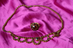 Antique garnets jewelry set. On the pink satin Royalty Free Stock Photo