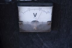 Antique gauge Voltmeter V=Voltage amplifier on wooden box for outdoor music. royalty free stock photography
