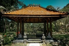 Antique gazebo pavilion with a roof asian style pagoda. In a summer tropical garden. A stone path along which the statues stand. Leads to the building. Inside stock photography