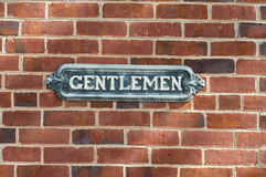 Antique gentlemen sign on red brock Royalty Free Stock Photos