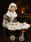 Antique girl and doll. Victorian style photo of a little girl playing with her doll Royalty Free Stock Photo
