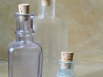 Antique Glass Bottles. Close-up of three antique glass bottles against a brown textured wall royalty free stock photo