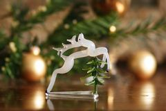 Antique glass deer figurine still life. Art deco hand glass jumping deer statue made in Czewchoslovakia in 1920s  1930s, with christmas tree and decorations in Stock Image