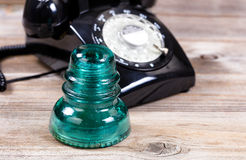Antique glass insulator and rotary dial phone on rustic wooden b Royalty Free Stock Photo