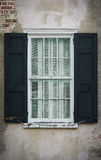 Antique glass window. Old window with hand-blown glass and handmade shutters on a weathered brick wall Stock Images