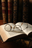 Geleerdheid. Antique glasses and books on an old wooden desk royalty free stock photo
