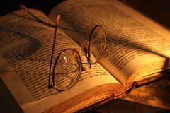 Geleerdheid. Antique glasses and books on an old wooden desk by candle light stock image