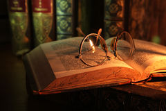 Geleerdheid. Antique glasses and books on an old wooden desk by candle light stock images