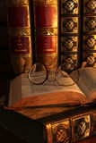 Geleerdheid. Antique glasses and books on an old wooden desk by candle light royalty free stock photos