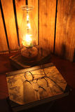Geleerdheid. Antique glasses and books on an old wooden desk by lamp light royalty free stock image