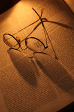 Geleerdheid. Antique glasses and books on an old wooden desk by lamp light royalty free stock images