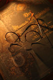Geleerdheid. Antique glasses and books on an old wooden desk by lamp light stock photography