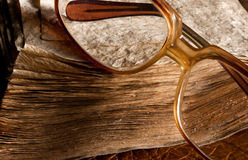 Antique glasses on old weathered book Stock Photography