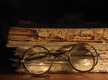 Antique glasses on old weathered book. Stock Images