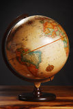 Antique globe. An antique globe on a table with a dark grey background royalty free stock photo