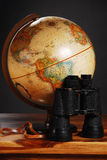 Antique globe. And Binoculars on a table, dark background royalty free stock photography