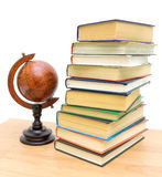 Antique globe and a stack of different books Stock Images