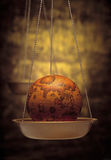 Antique globe on weight scale Royalty Free Stock Images