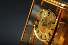 Antique gold clock. An antique gold clock with Roman numerals on black background Stock Photo