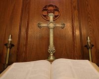 Antique gold cross behind open blurry Bible stock photo