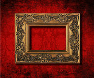 Antique gold frame. On a grungy Victorian velvet wallpaper background Stock Photos