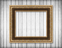 Antique gold frame on white wooden wall ; Empty picture frame Royalty Free Stock Image