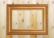 Antique gold frame on white wooden wall ;. Empty picture frame o Stock Image