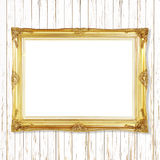 Antique gold frame on white wooden wall ;. Empty picture frame o Royalty Free Stock Photo