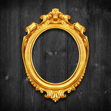The Antique gold frame on wooden wall;. Empty Antique gold pictu Stock Image