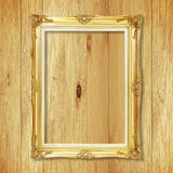 Antique gold frame on wooden wall ;. Empty picture frame on whit Stock Images