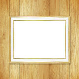 Antique gold frame on wooden wall ;. Empty picture frame on whit Royalty Free Stock Images