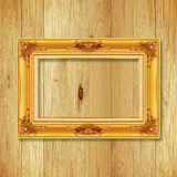Antique gold frame on wooden wall ;. Empty picture frame on whit Stock Photography