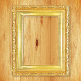 Antique gold frame on wooden wall;. Empty picture frame on woode Royalty Free Stock Images