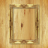 Antique gold frame on wooden wall. Empty picture frame on white wooden wall Stock Image