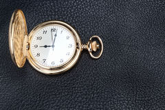 Antique gold pocket watch on a textured black leather Royalty Free Stock Image