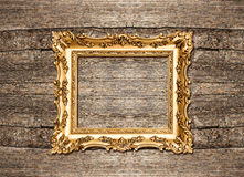 Antique golden frame over rustic wooden background Royalty Free Stock Photo