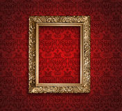Antique golden frame on red wallpaper. Royalty Free Stock Images