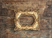 Antique golden frame on used wooden background. Rustic texture Stock Photos