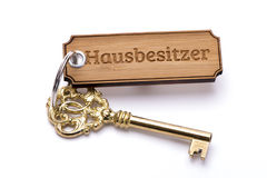 Antique golden house key on keyring. With print in german language for house owner: Hausbesitzer Stock Photography