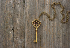 Antique golden key over wooden background Stock Photos