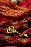 Antique Golden Key on Red Luxury Fabric Stock Images