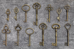 Antique golden keys. Row of antique golden keys on a grunge wooden background Royalty Free Stock Photo