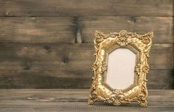 Antique golden picture frame on wooden background Stock Photos