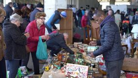 Antique goods seller sells a rare item to a woman at a flea market