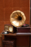 Antique gramophone with golden horn and radio. On table on vintage brown wall background Royalty Free Stock Photo