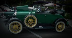 Antique green automobile with the seat in the boot. Totally redone antique car with wire spokes.  It was seen at the Green Lake yearly car show in the Seattle Stock Image