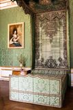 Antique green canopy bed in a stately interior. Antique green canopy bed with fabric upholstery in a stately interior with matching textile covering the wall and stock photo