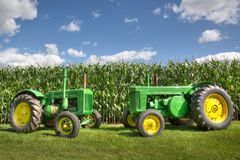 Antique Vintage Green John Deere Tractors in front of a corn field with a blue sky. Vintage antique John Deere green tractors next to a corn field in Ontario royalty free stock photography